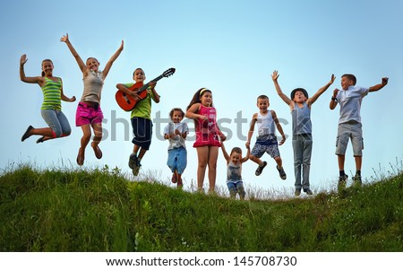happy kids jumping on summer field - stock photo
