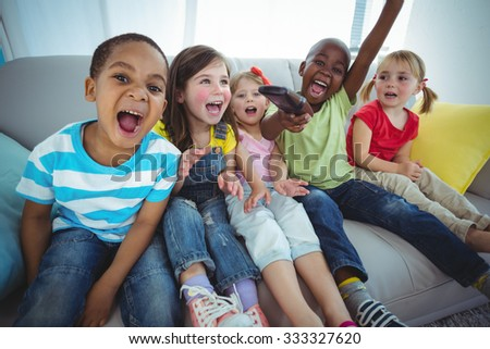 Happy kids laughing while sitting down on the couch - stock photo