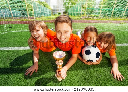 Happy kids laying on grass with golden goblet