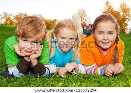 happy kids laying on green grass in autumn park - stock photo