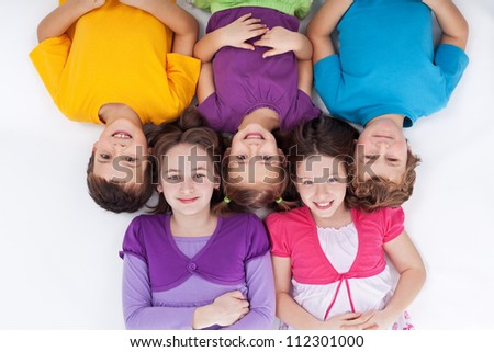 Happy kids lying on the floor with heads sticked together in a row - stock photo