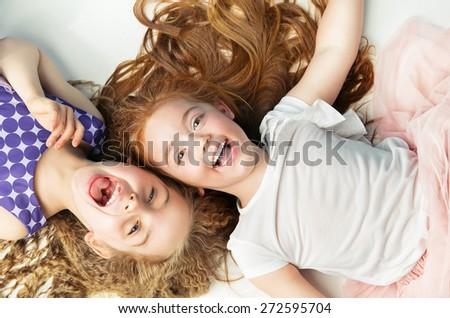 Happy kids lying on white background - stock photo