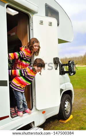 Happy kids near camper (RV) having fun, family vacation trip in motorhome  - stock photo