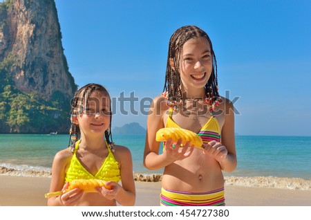 Happy kids on beach family vacation, children having fun and eating pineapple tropical fruit  - stock photo
