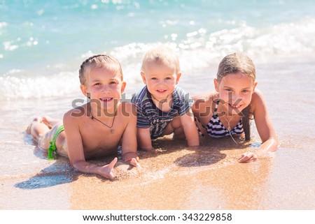 Happy kids on the beach having fun - stock photo