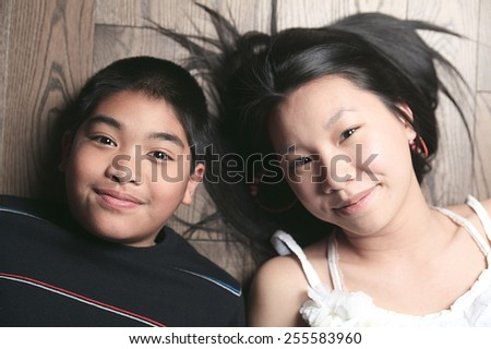 happy kids on the floor laying on wooden floor - stock photo