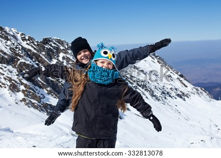 Happy kids on the top of mountain - enjoying the first snow - stock photo