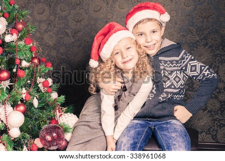 Happy kids or children at Christmas holiday near decorated christmas tree. New Year. Concept of family celebration - stock photo