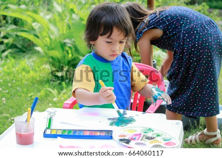 Happy kids painting .Activity outdoor in summer.
