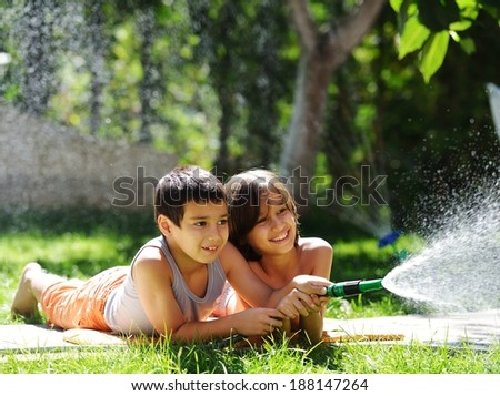 Happy kids playing and splashing with water sprinkler on summer grass yard - stock photo