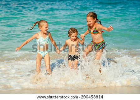 happy kids playing on beach at the day time - stock photo
