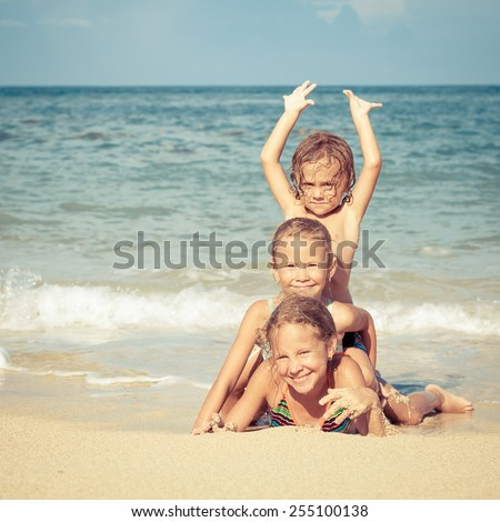 happy kids playing on beach at the day time. Concept Brother And Sister Together Forever - stock photo