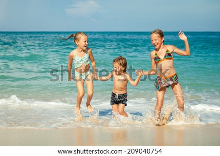 Happy kids playing on beach at the day time. Concept of friendly family. - stock photo