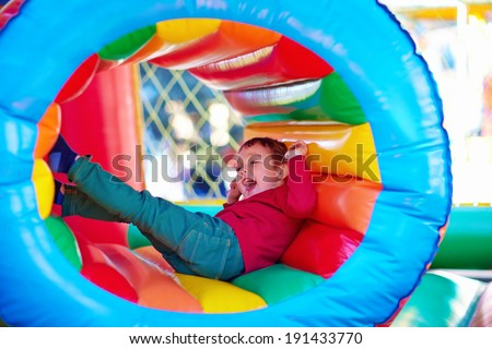 happy kids playing on inflatable attraction playground - stock photo