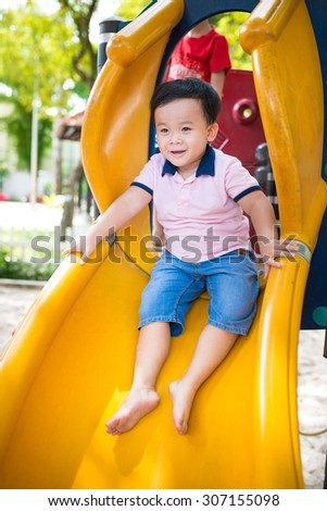 Happy kids playing on slide at school playground  - stock photo