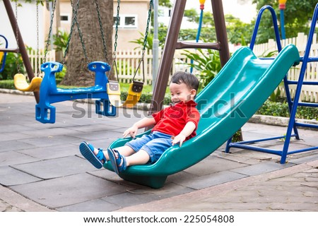 Happy kids playing on slide. Lovely school aged asian child on the chute - stock photo