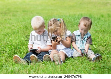 Happy kids playing on smartphones sitting on the grass in the park. Brothers and sister.  - stock photo