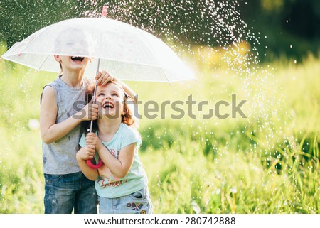 happy kids playing outdoor in raining spring park. shallow depth of field,focus on children or raindrops - stock photo