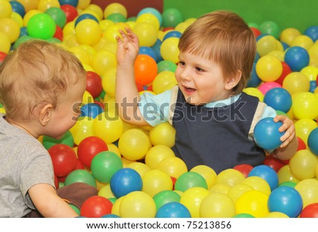 happy kids playing with colored balls - stock photo