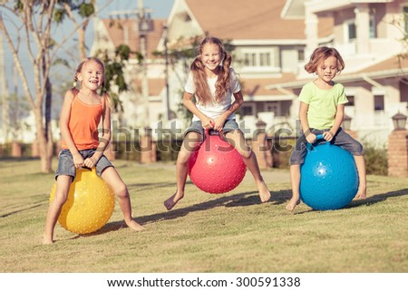 happy kids playing with inflatable balls on the lawn in front of house at the day time - stock photo