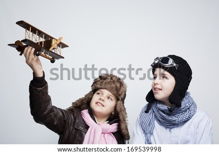 Happy kids playing with toy airplane against gray background - stock photo