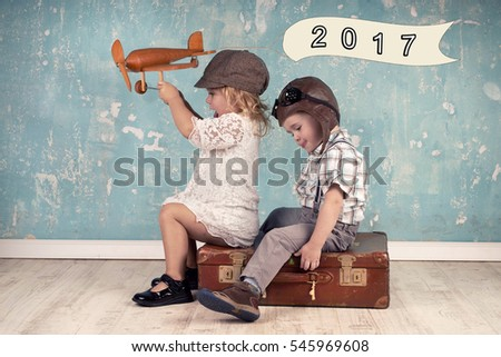 Happy kids playing with vintage wooden airplane. happy new year concept - 2017