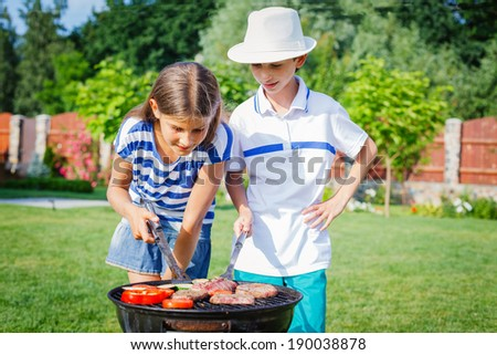 Happy kids preparing meat and vegetables using a barbecue grill - stock photo