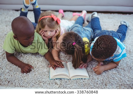 Happy kids reading a book together on the floor - stock photo