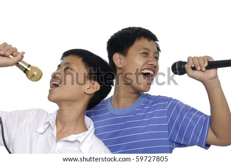 Happy kids singing into microphone - stock photo