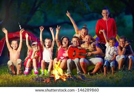 happy kids singing songs around camp fire - stock photo