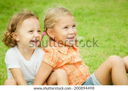 Happy kids sitting on the grass. Concept Brother And Sister Together Forever