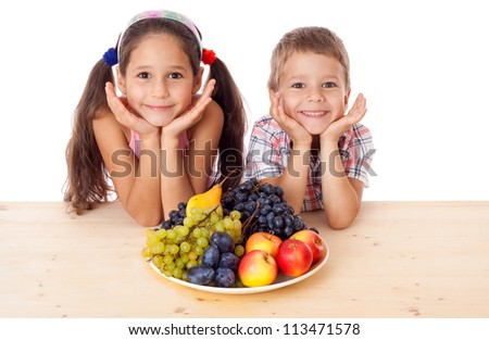 Happy kids sitting on the table with plate of fruit, isolated on white - stock photo