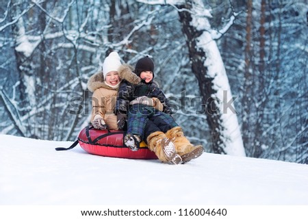 Happy kids slide down the hill. Forest and a lot of snow. Cold winter. - stock photo