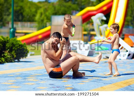 happy kids splashing the water on father in aquapark - stock photo