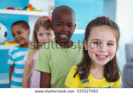 Happy kids standing in a line looking at the camera