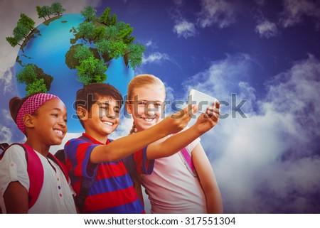 Happy kids taking selfie in school corridor against digitally generated earth floating in air - stock photo