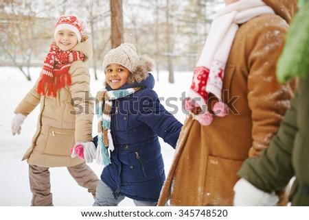 Happy kids taking walk in winter park - stock photo