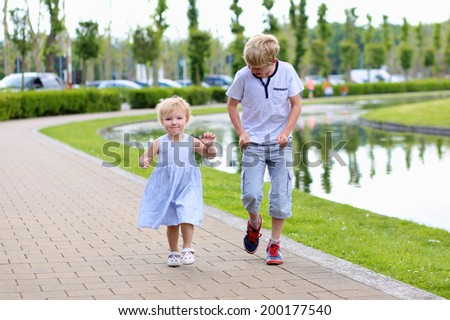 Happy kids, teenager school boy and his little sister, adorable toddler girl, playing in city park, running together along small river - stock photo