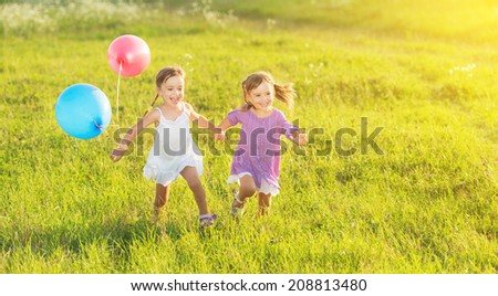 happy kids twin sisters running around laughing and playing with balloons in the meadow in summer - stock photo