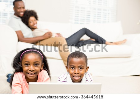 Happy kids using laptop pc beside their parents - stock photo