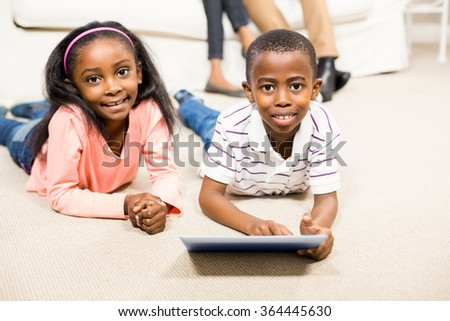Happy kids using tablet pc beside their parents - stock photo
