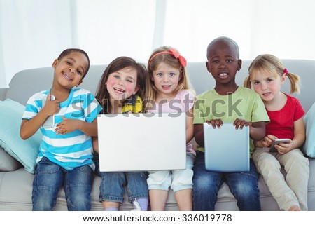 Happy kids using technology while sitting on the couch - stock photo