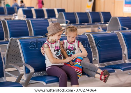 Happy kids waiting for flight inside international airport. Flight delay - stock photo