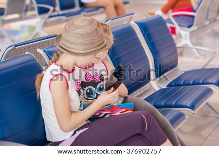 Happy kids waiting for flight inside international airport, playing with tablet PC. Flight delay concept