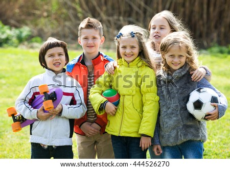 Happy kids with ball having fun outdoors in sunny day - stock photo