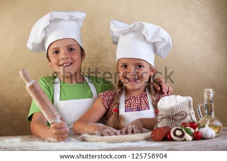 Happy kids with chef hats making pizza toghehter - stretching the dough - stock photo