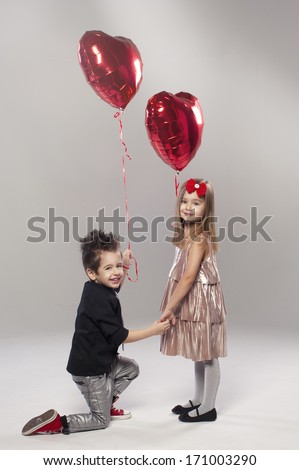 Happy kids with red heart balloon on a light background