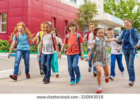 Happy kids with rucksacks walking holding hands - stock photo