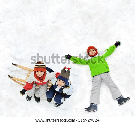 Happy kids with sledding on snow ground - stock photo