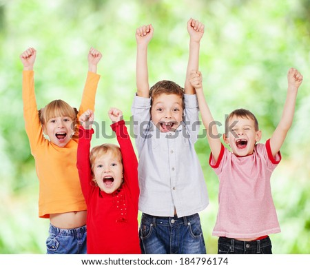 Happy kids with their hands up outdoors - stock photo